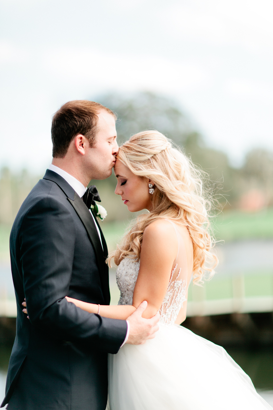 Image of a groom kissing the forehead of his bride on their wedding day at TPC Sawgrass in Ponte Vedra, Florida