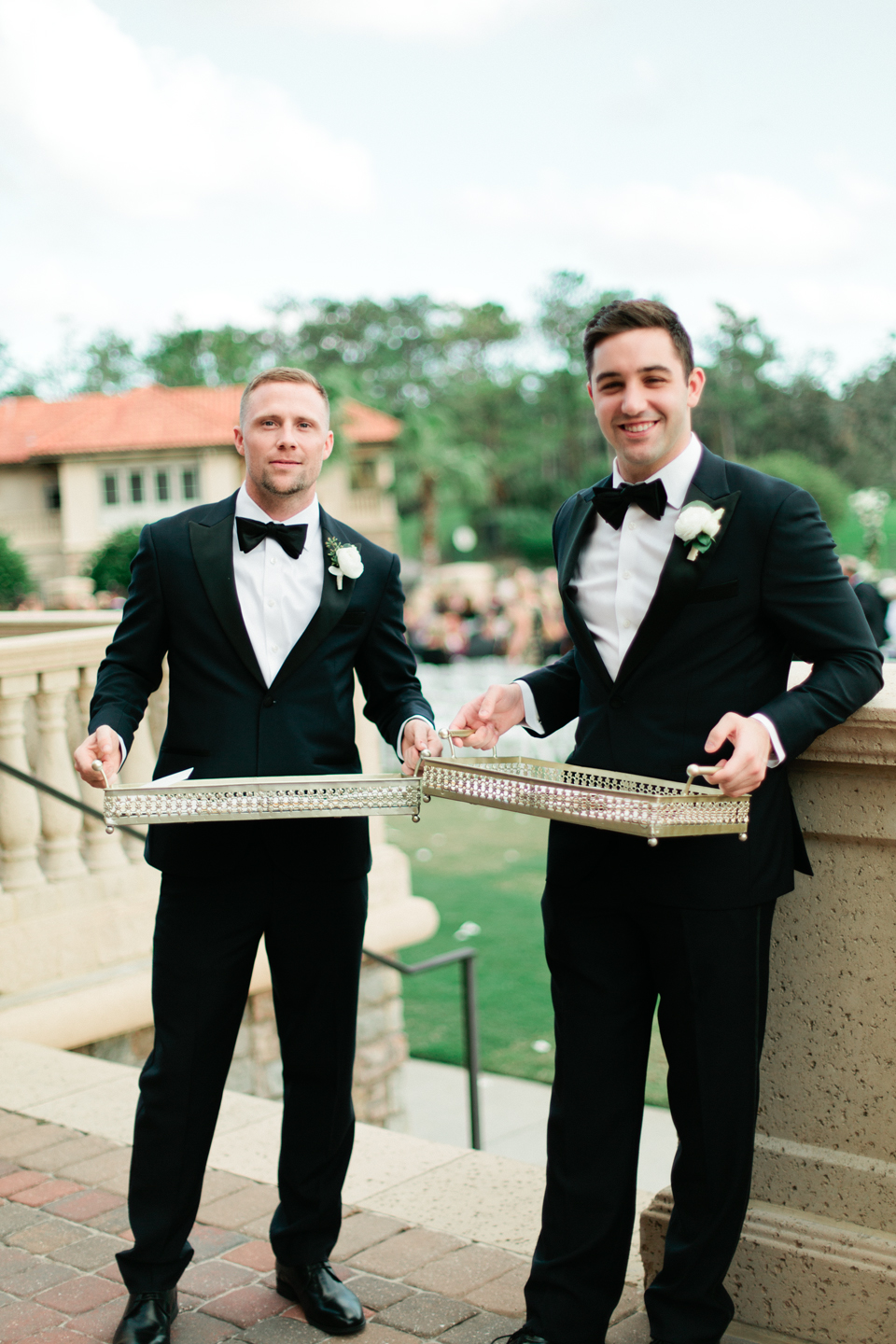 Picture of ushers at a wedding, wearing black tuxedos handing out programs at TPC Sawgrass in Ponte Vedra, Florida