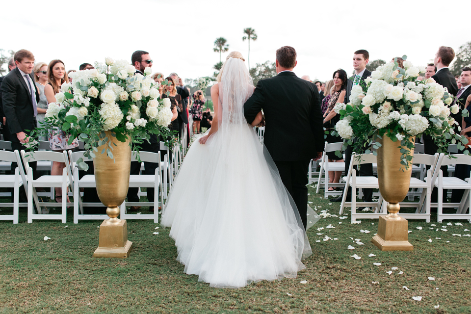 Image of a bride walking down the aisle with her father on her wedding day at the TPC Sawgrass in Ponte Vedra, Florida