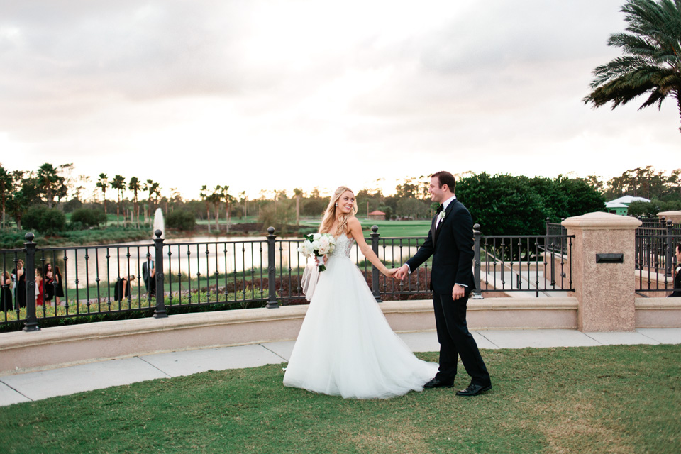 Image of a bride and groom walking hand in hand on their wedding day with the sun setting at TPC Sawgrass in Ponte Vedra, Florida