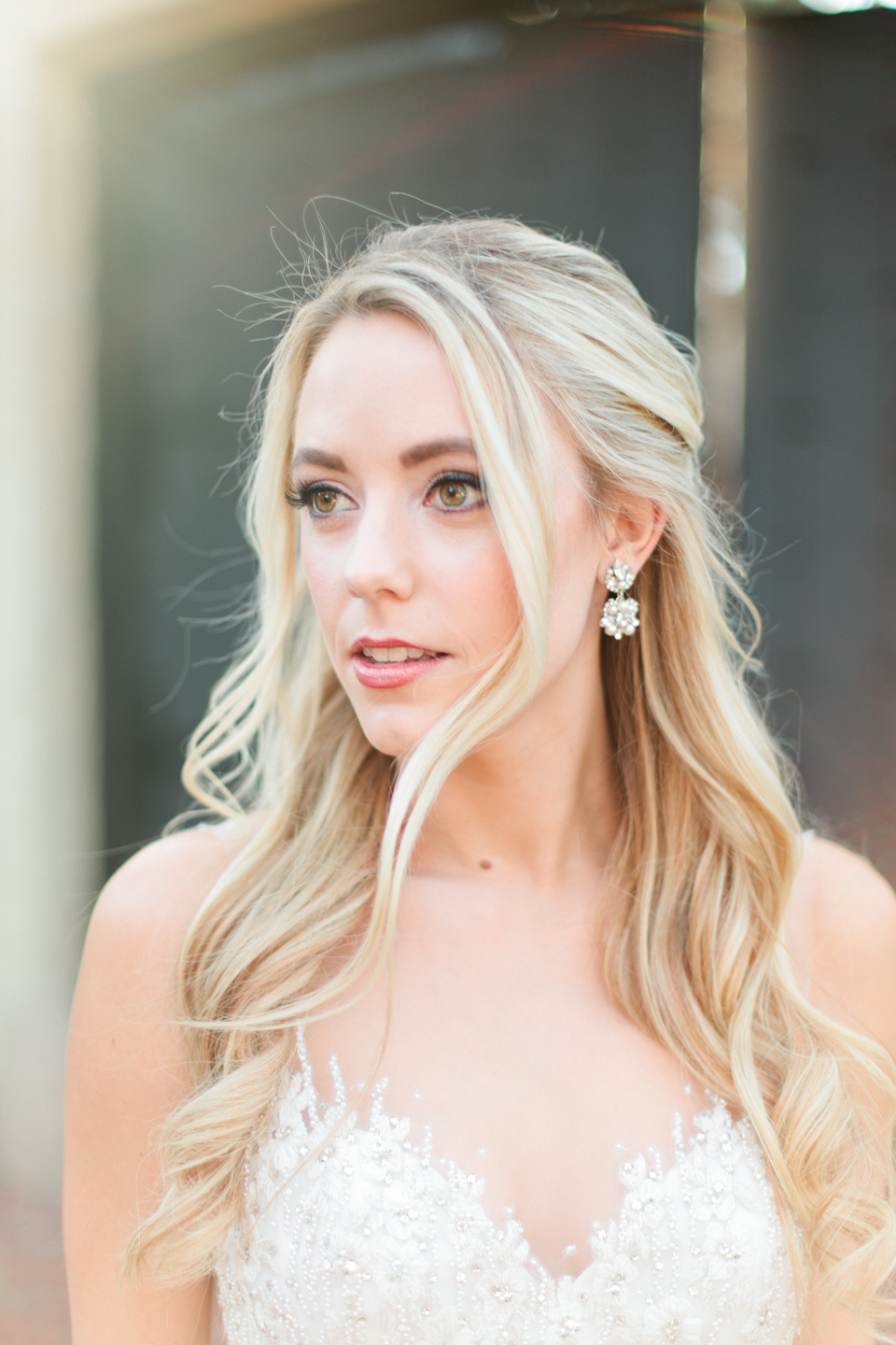 Image of a close up of a bride with her hair curled, diamond earrings and a Calvet Couture bridal gown.  She is in front of Epping Forest Yacht Club in Jacksonville, Florida