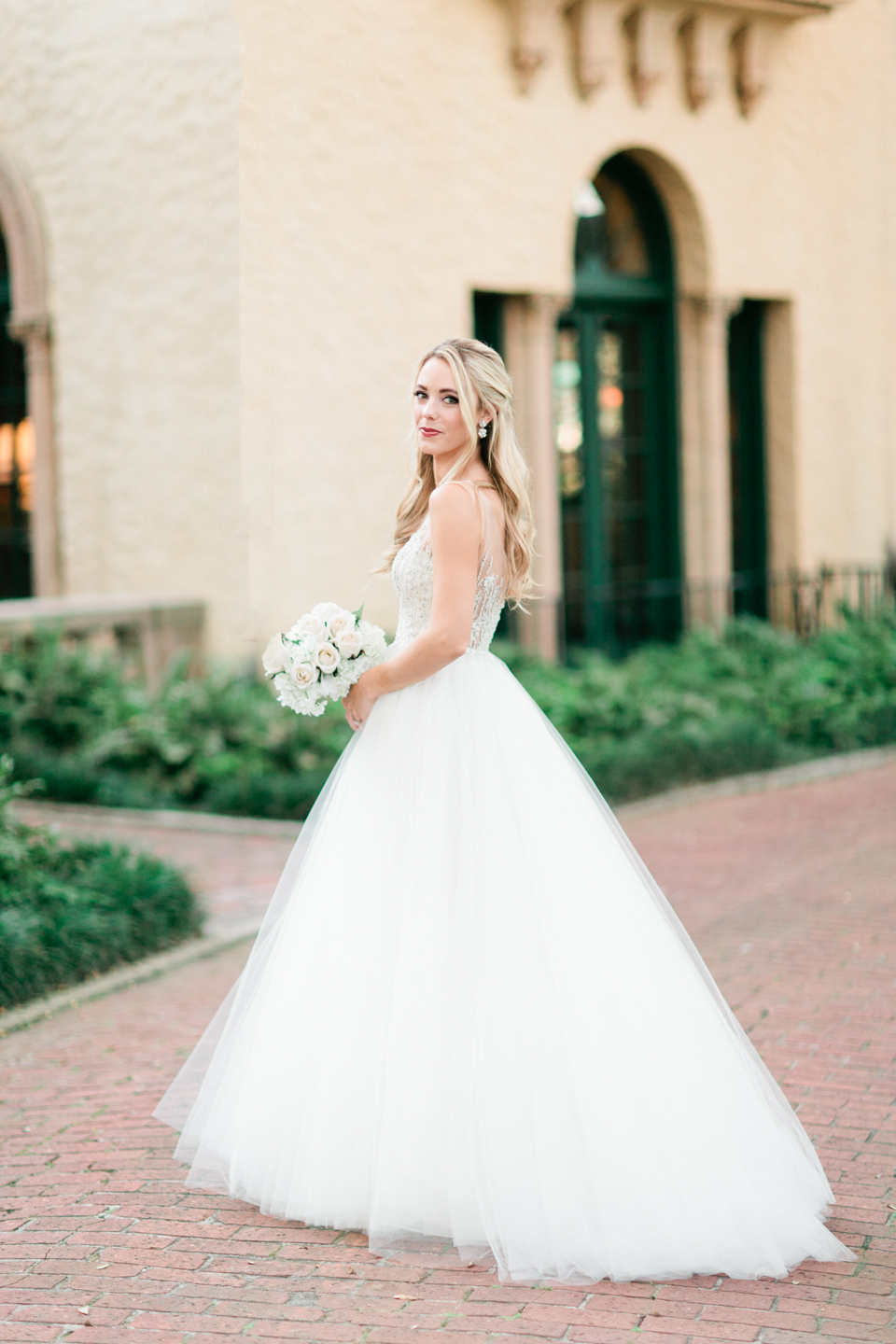 Image of a bride in a wedding gown in front of the Epping Forest Yacht Club in Jacksonville, Florida.  She is wearing a gown from Calvet Couture and holding a white bouquet.