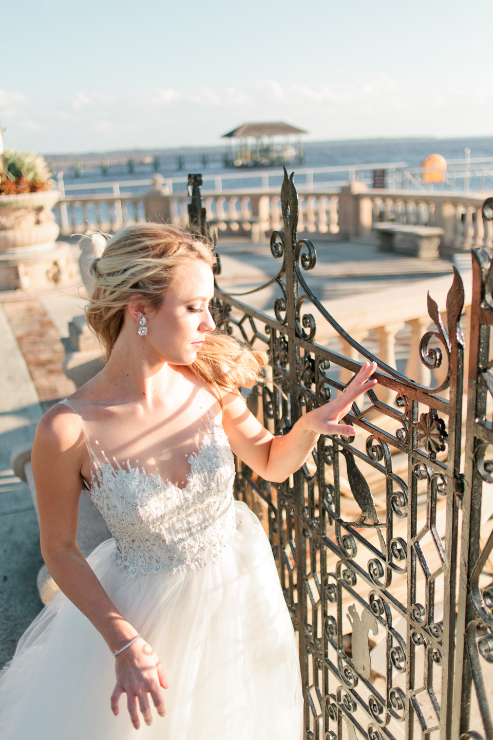 Image of a bride at an iron gate, looking out over the water in her Calvet Couture bridal gown.  The bride is at the Epping Forest Yacht Club in Jacksonville, Florida