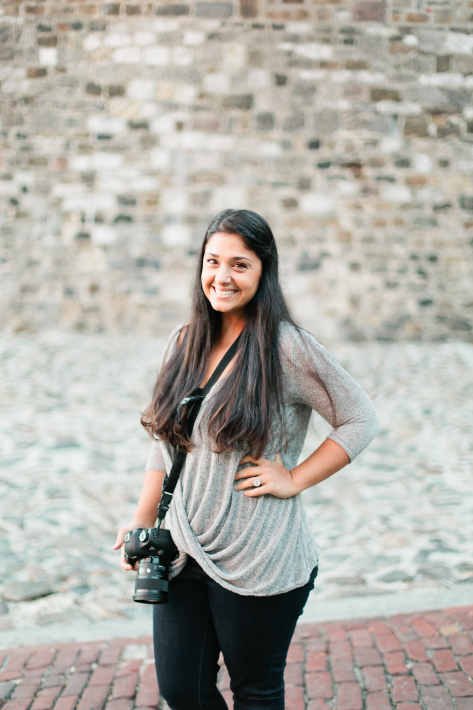Picture of a female photographer in historic downtown Savannah, Georgia.  She is wearing a grey shirt, black pants, and is holding a Canon camera.  This is Rana of Roohi Photography.