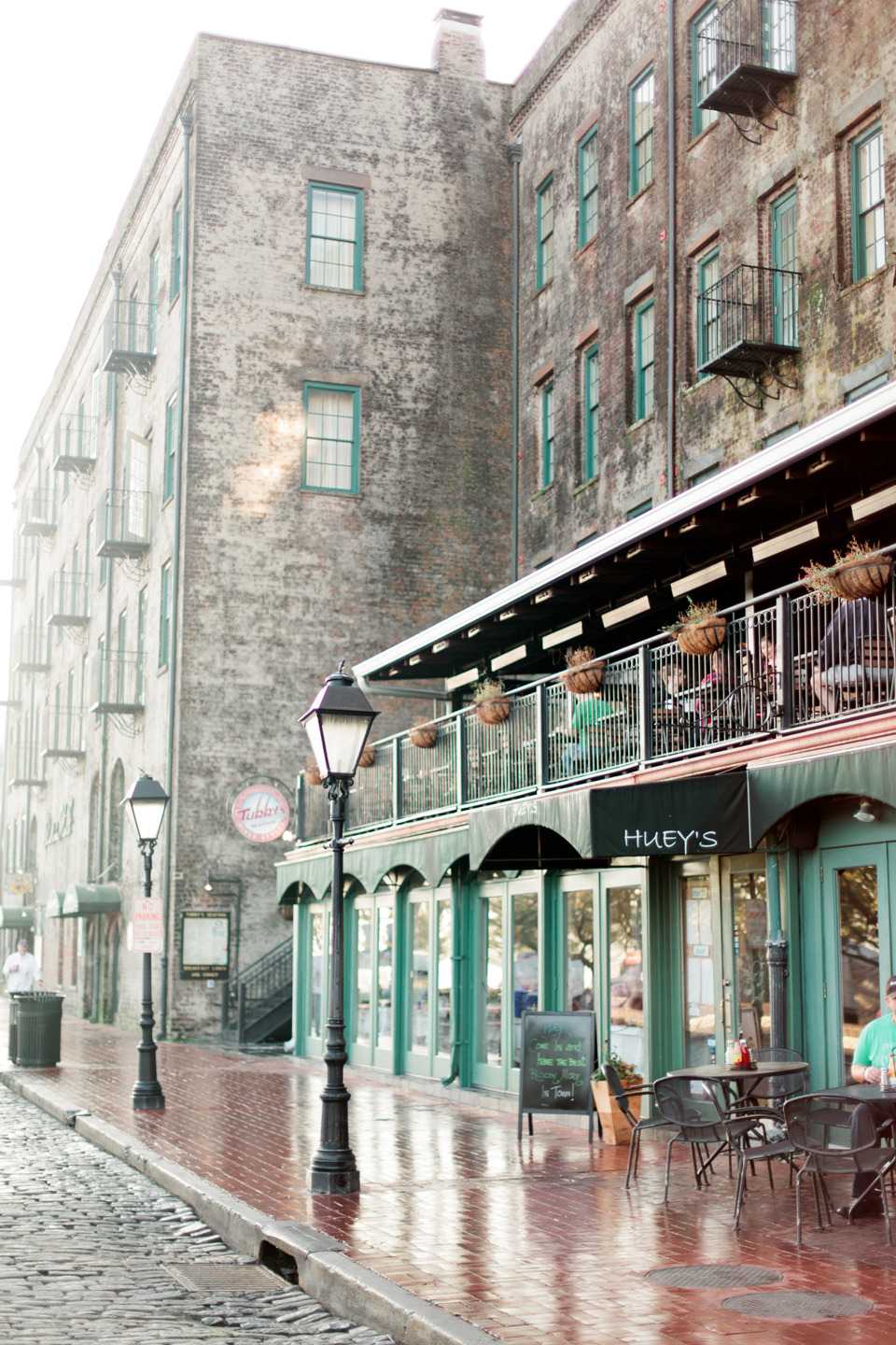 Image of East River Street in historic downtown Savannah.  There is a cobblestone street with a sidewalk cafe and lamp posts.