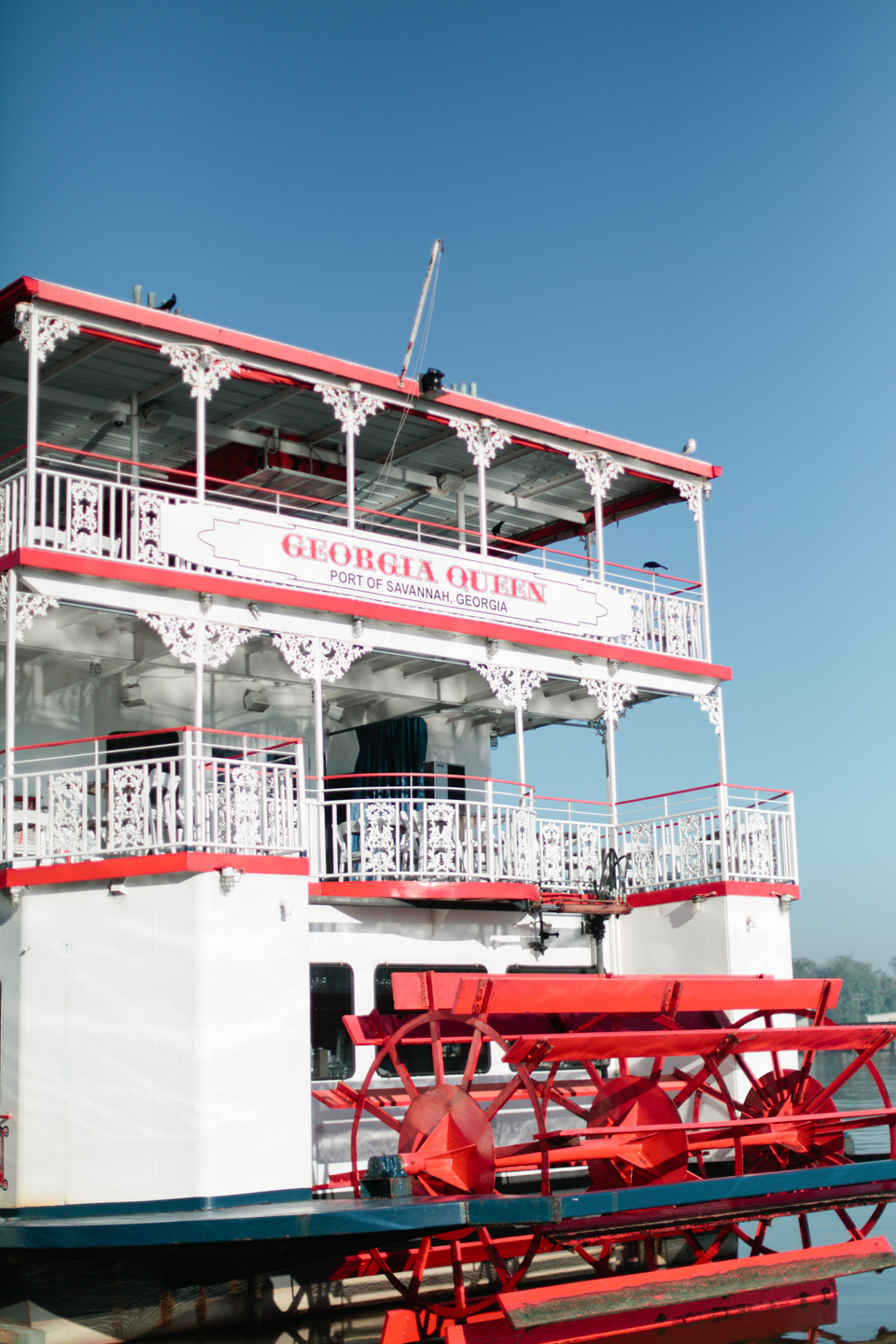 Picture of a white and red riverboat docked on East River Street in historic downtown Savannah, Georgia.