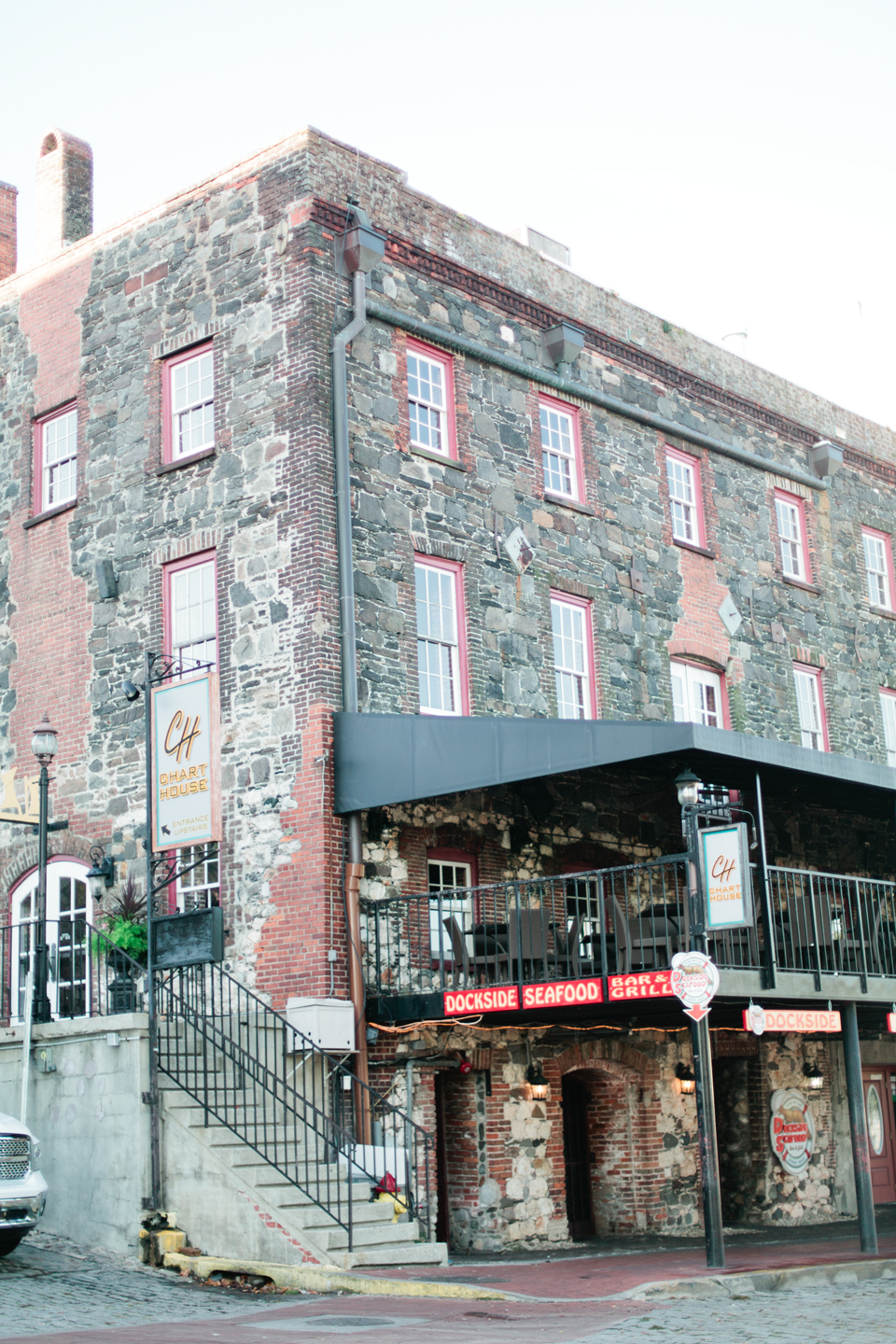 Image of buildings on East River Street in downtown historic Savannah, Georgia.  This is a four story stone building with steps.