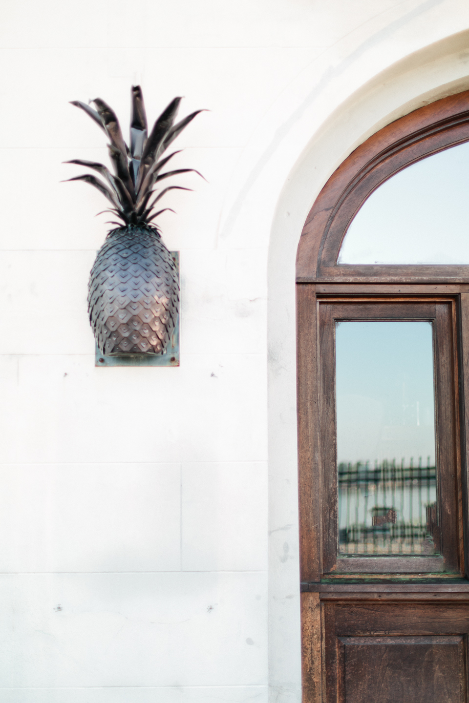 Picture of the outside of a building with wooden doors, glass panes, and an iron pineapple sconce.  East River Street in historic downtown Savannah, Georgia.
