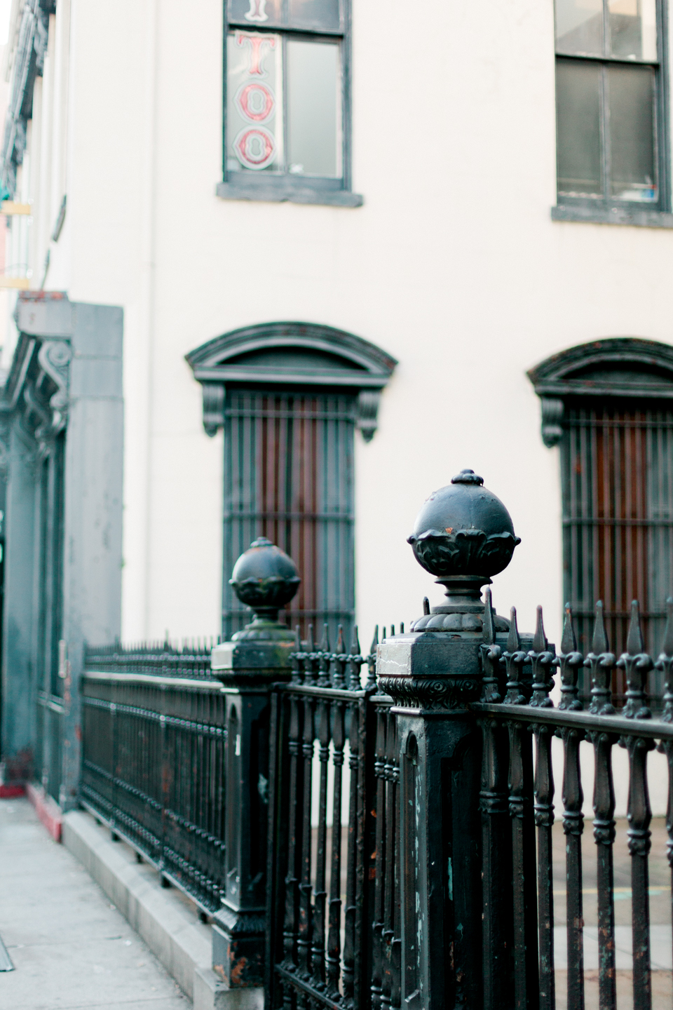Image of downtown historic Savannah, Georgia.  Iron fence with architectural posts and a historic building beside it.