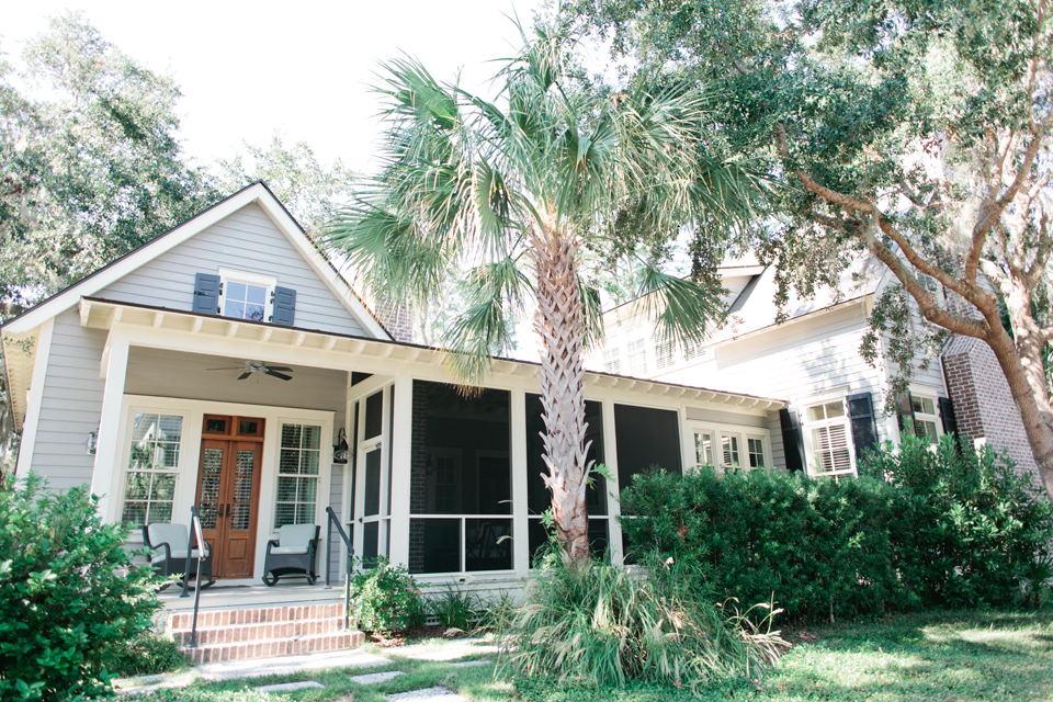 Image of a coastal South Carolina house in Montage Palmetto Bluff.  One story, pale blue, with a front porch.