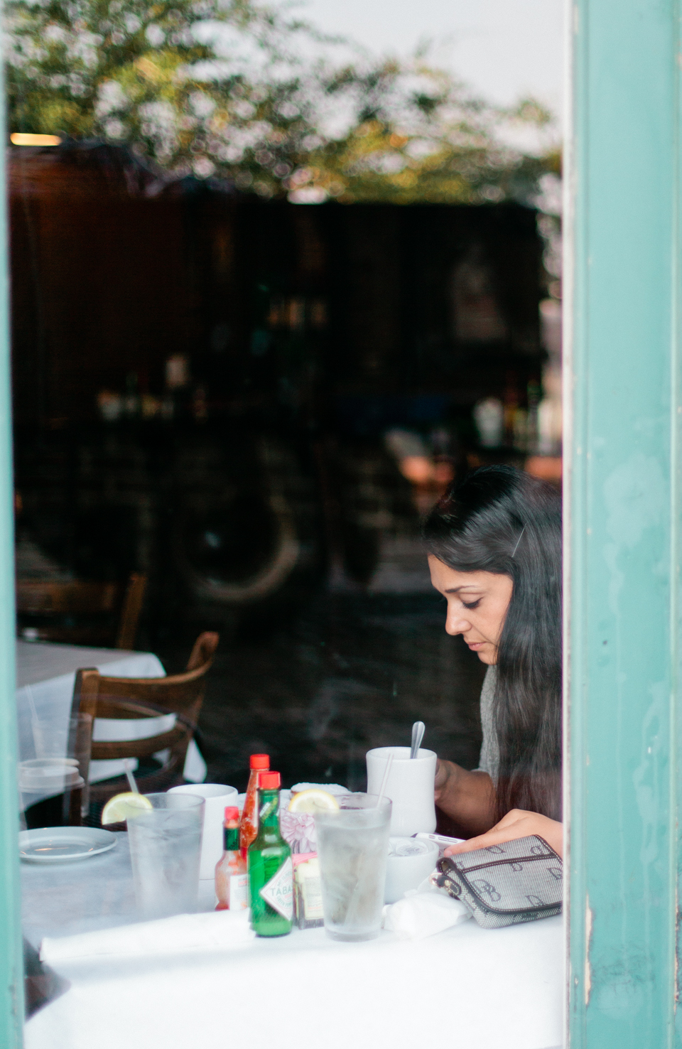 Image of Rana of Roohi Photography through a cafe window in historic downtown Savannah, Georgia.