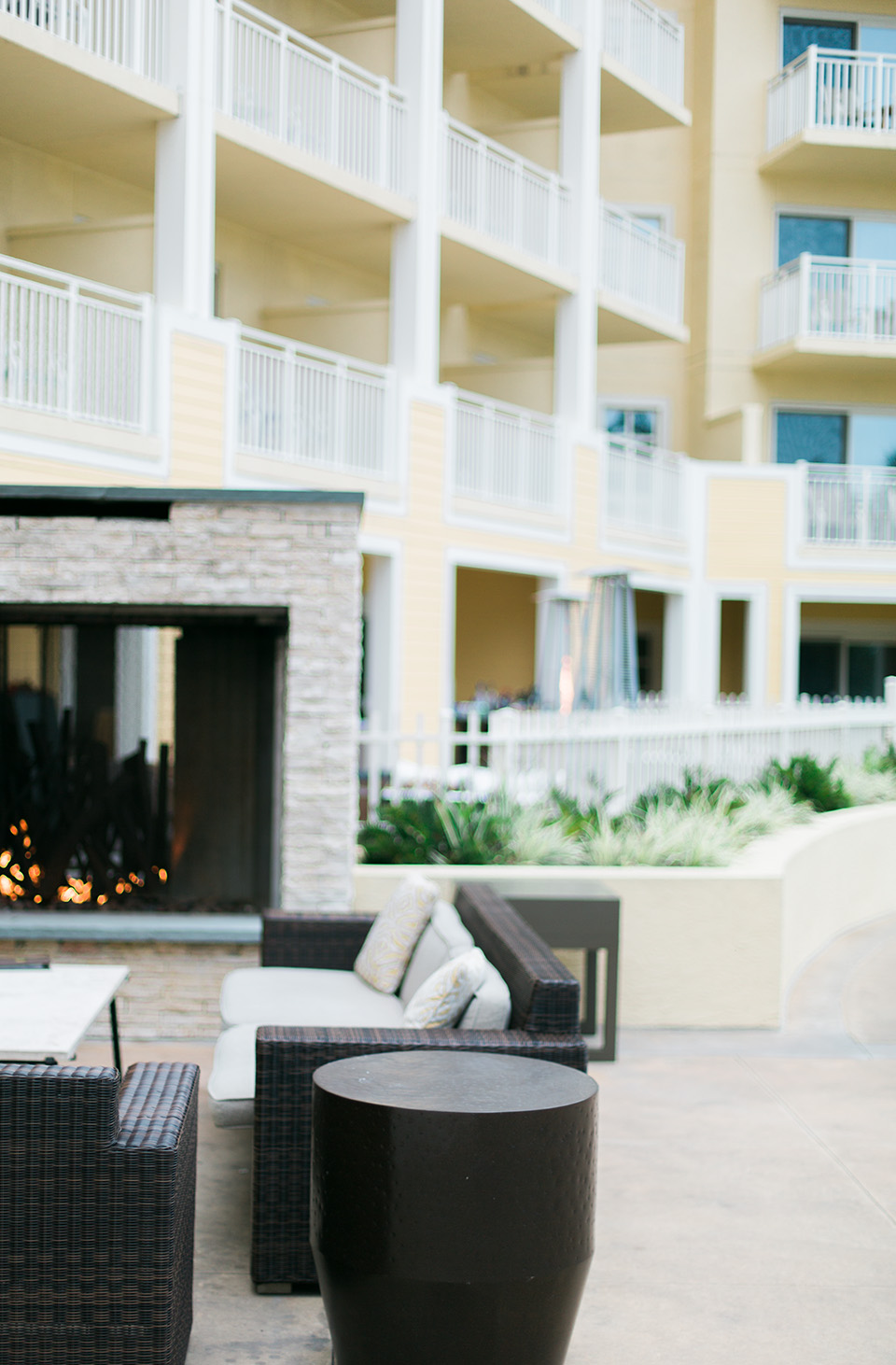 Image of one of the outdoor lounge areas at the Omni Amelia Island Plantation Resort.  There is a fireplace and comfortable furniture for sitting.