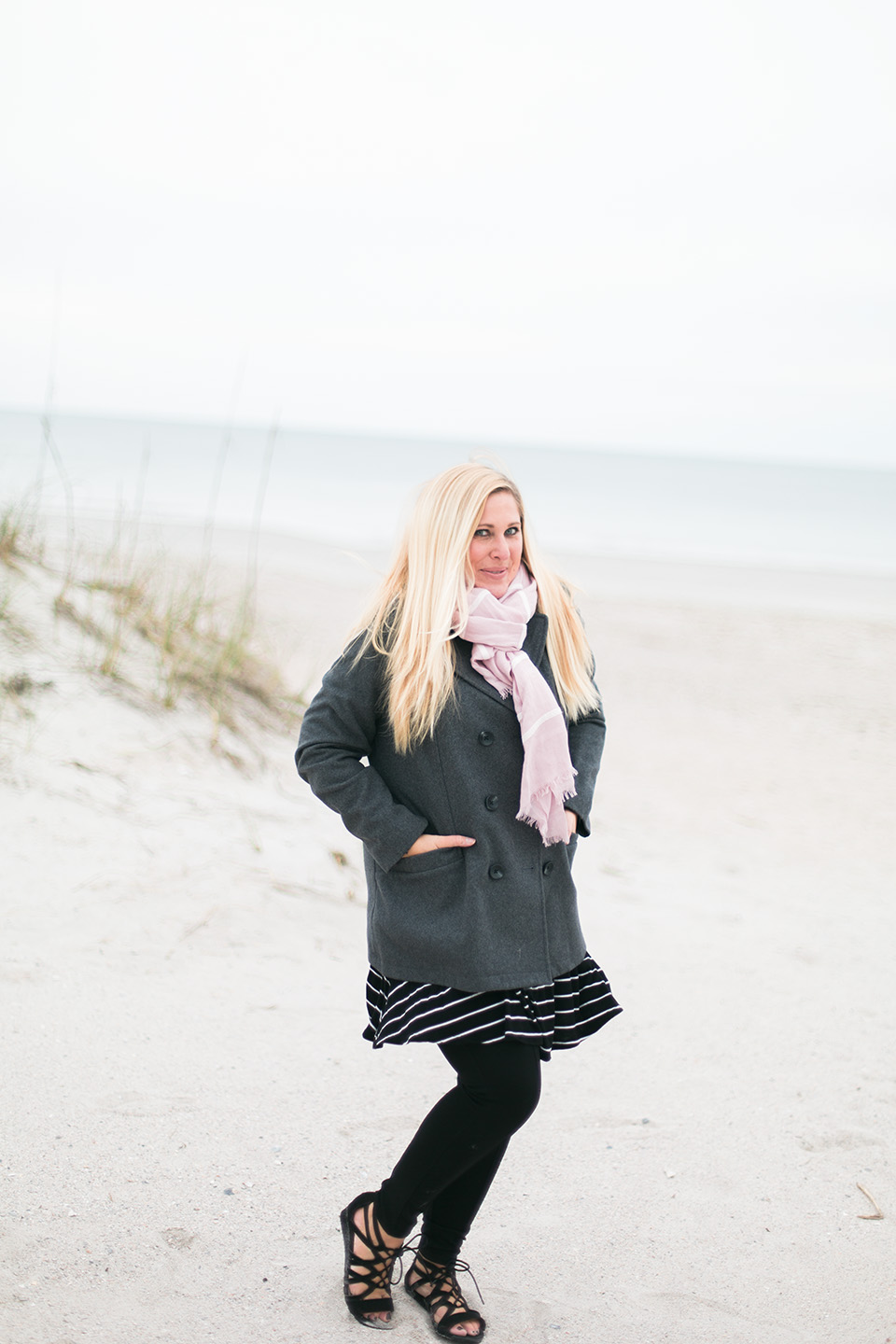 Picture of a woman in a coat and scarf on the white sand beach of the Atlantic coast at Omni Amelia Island Plantation Resort.
