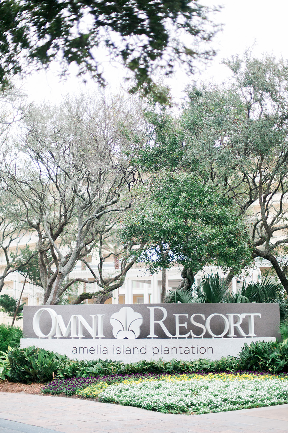 "This is a picture of the entrance to the Omni Amelia Island Plantation Resort.  There is a sign with large letters, ""Omni Resorts"" with a flower in the middle of the sign."