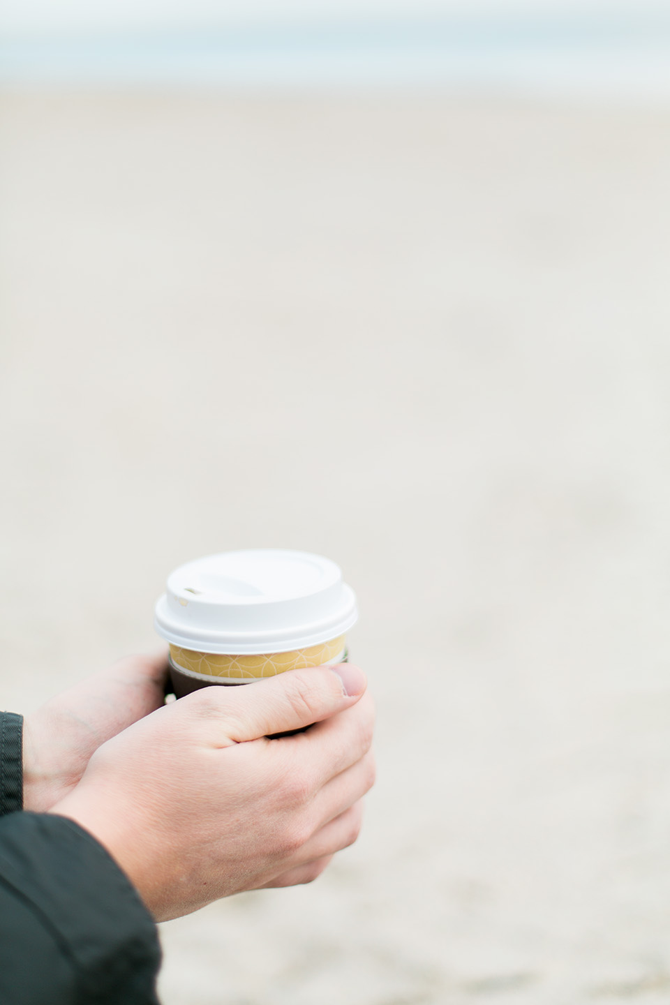 Image of a man holding a cup of coffee with a lid on a beach at Omni Amelia Island Plantation Resort.