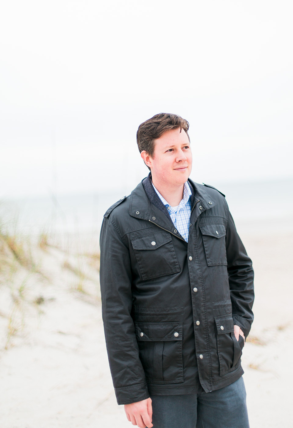Image of a man on the beach with a black leather coat at the Omni Amelia Island Plantation Resort.