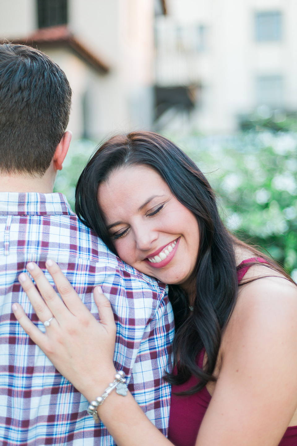 Image of an engaged couple in downtown Orlando, Florida.  The woman is closing her eyes and resting her head on her fiance's shoulder.  You can see her engagement ring on her left ring finger.