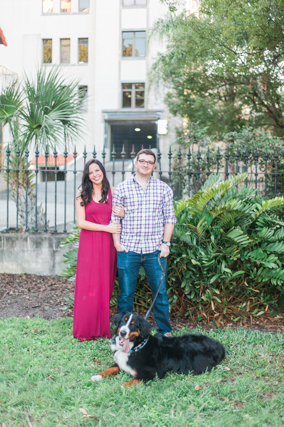 Image of an engaged couple standing together, linking arms, with their Bernese Mountain Dog downtown Orlando, Florida.  They are standing on grass in front of a black iron gate.