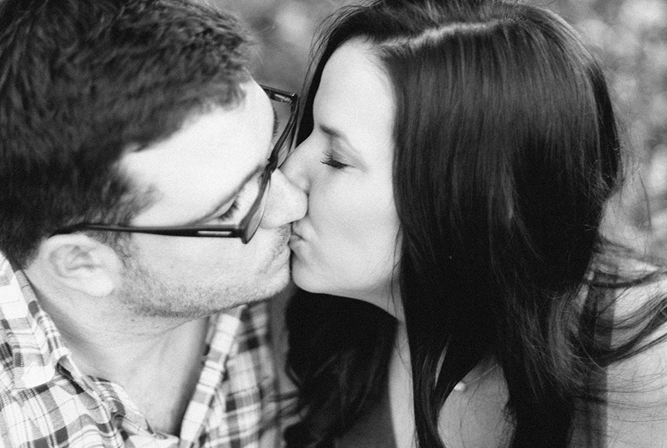 A black and white picture of an engaged couple kissing in downtown Orlando, Florida.