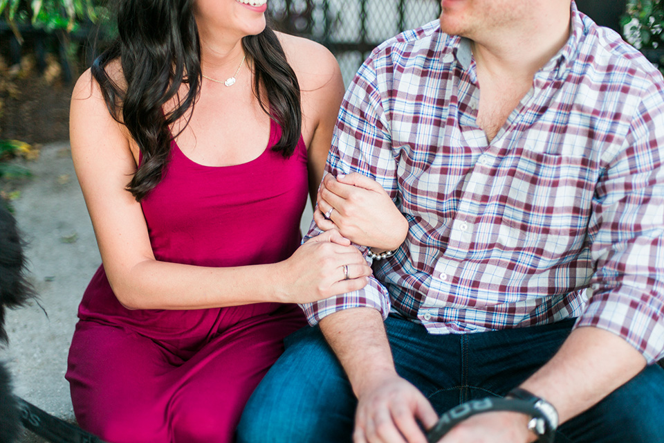 Image of an engaged couple linking arms and looking at each other lovingly.  They are both sitting on steps in front of a gate in downtown Orlando, Florida