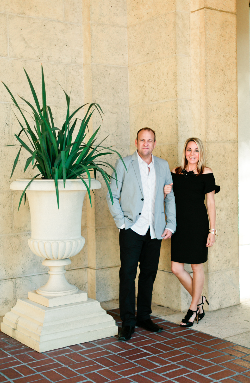 Image of a couple standing in front of the Museum of Fine Arts downtown St. Pete.  There is a large urn with greenery and cream stone exterior.