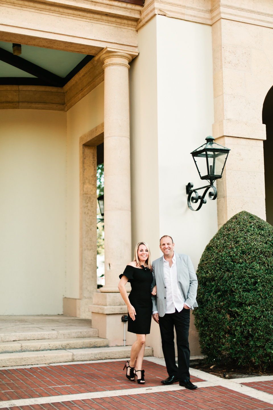 Picture of a couple standing in front of the Museum of Fine Arts downtown St. Pete.  The woman is wearing a short black dress with ruffle sleeves.  The man is wearing dress pants and a sportscoat.