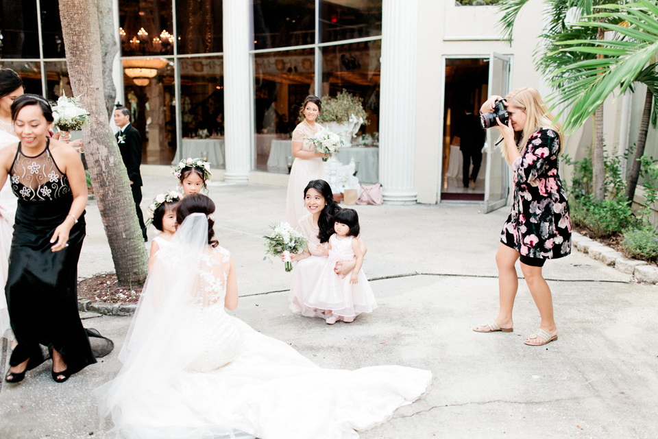 Image of a bride and her child attendants getting their picture taken by Debra Eby Photography, Fine Art Jacksonville Photographer.  This is a wide shot showing the background as well.