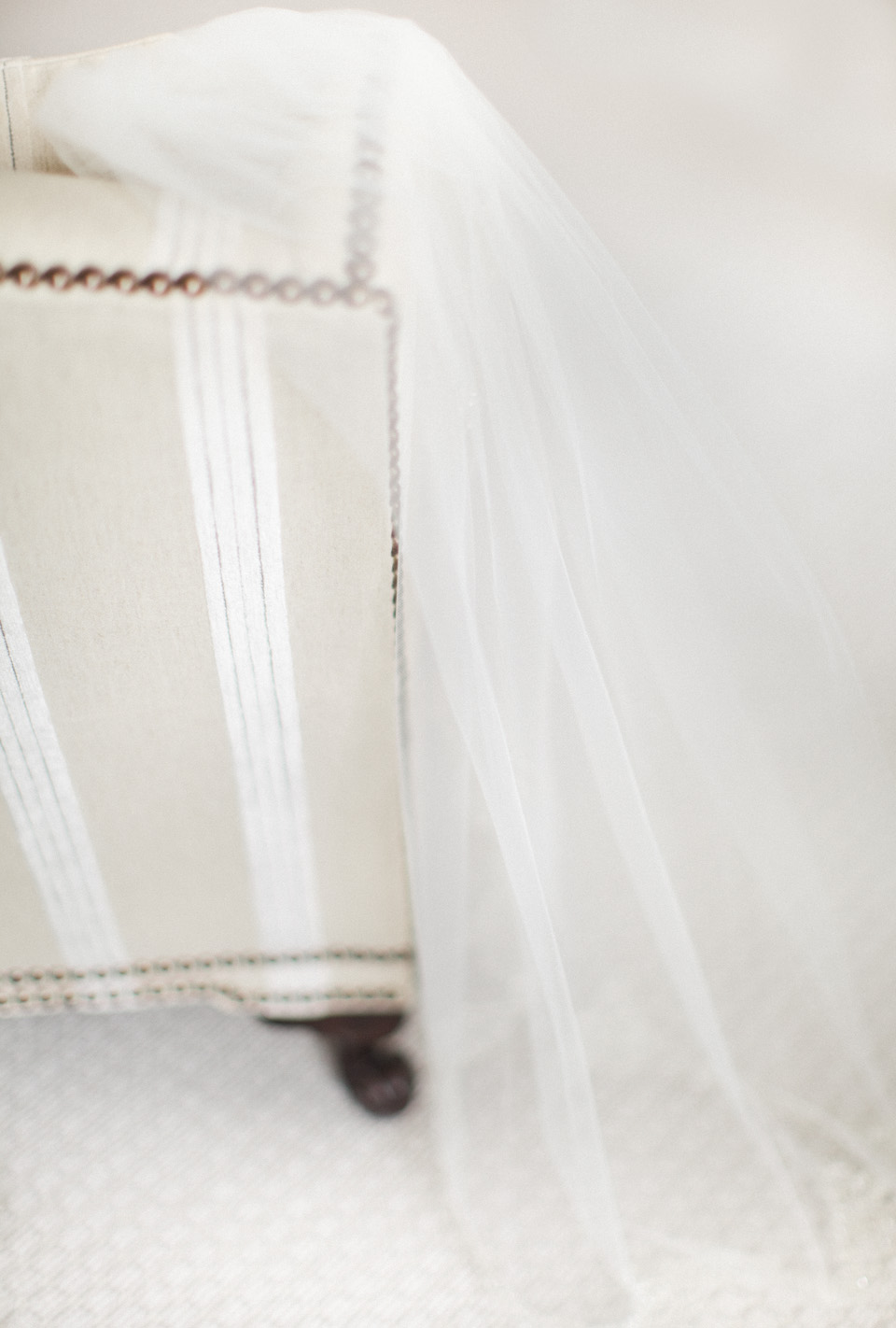 Image of a veil carefully sitting on a white striped plush chair.