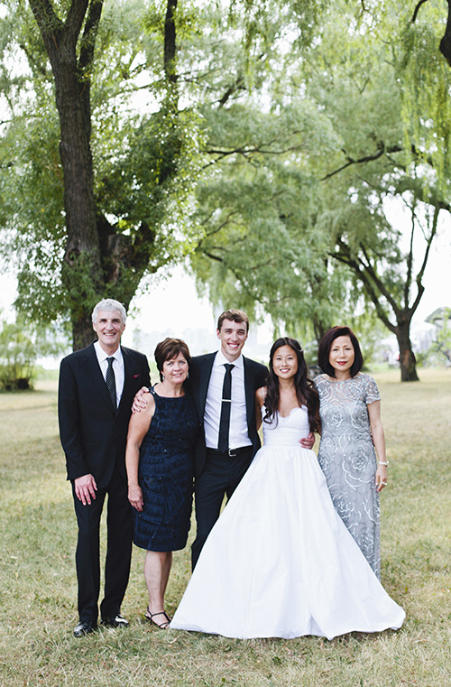 Picture of a family portrait on a wedding day.  There are large trees in the background and a lake behind them.