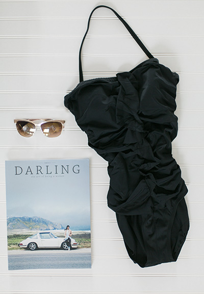 """Image of a little black swimsuit with the magazine """"Darling"""" and large sunglasses.  Image by 