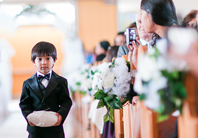 Image of a wedding guest taking a picture of a ring bearer as he walks down the aisle of the ceremony.  | Debra Eby Photography Co.