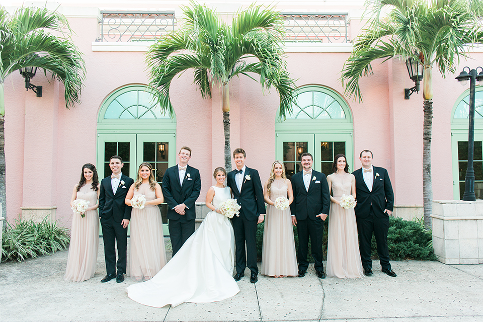 Image of a bridal party posing on a wedding day.  The wedding is at The Vinoy in St. Petersburg, Florida.  There are palm trees and a pink ballroom in the background.