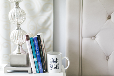 "Picture of a nightstand with books and a mug, propped up against a lamp.  The mug has hand lettering on it that says, ""Hot Stuff"". 