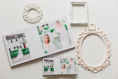 Picture of a luxury wedding album and parent album.  They are both layflat design with high end printing.  White frames surround them both on a white backdrop.  | Debra Eby Photography Co.