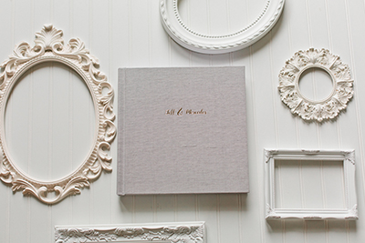Picture of a luxury wedding album with gold lettering.  Picture frames surround the album on a white backdrop. | Debra Eby Photography Co.