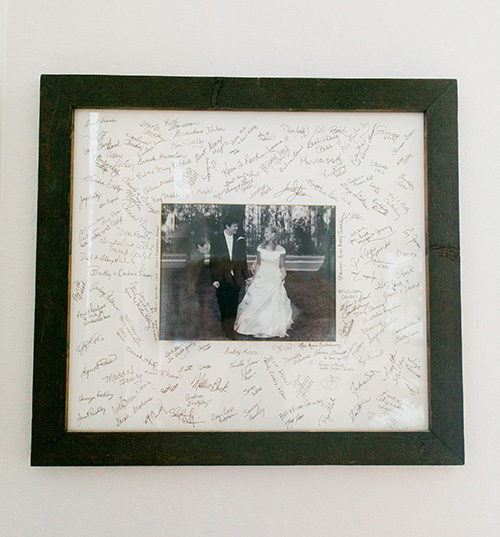 Picture of a frame used as a guestbook on a wedding day.  Picture of a bride and groom portrait in side of the frame.  | Debra Eby Photography Co.