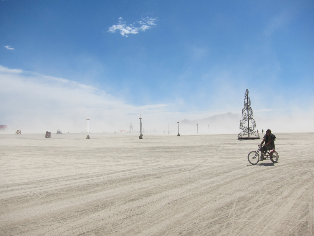 a cyclist takes an early morning ride on the open playa