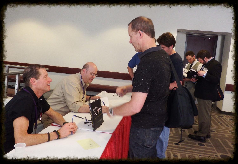 David Meerman Scott (left) and Richard Jurek (right), sign books for fans at Space Fest VI in Pasadena, California.