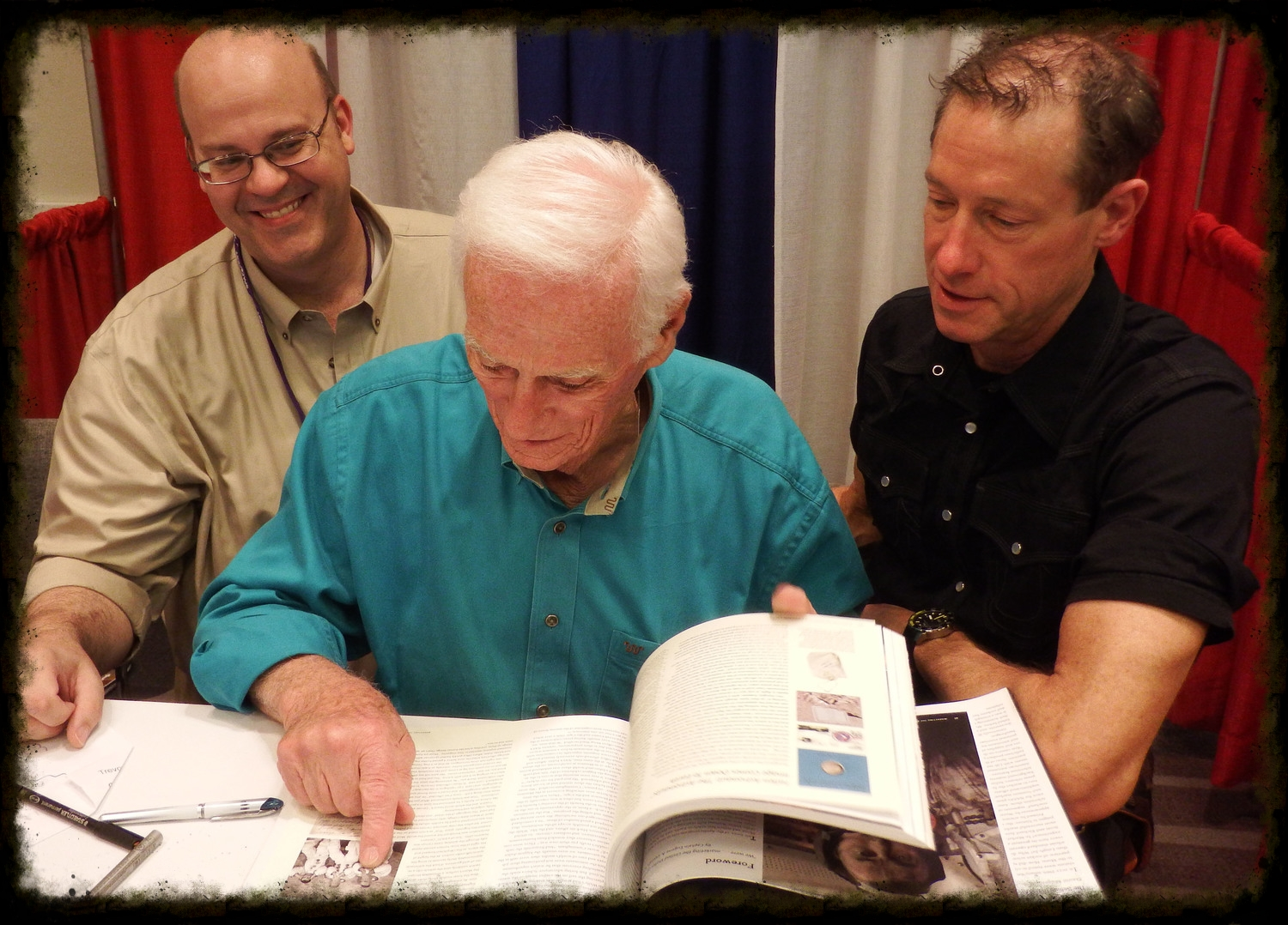 Richard Jurek (left), Astronaut Gene Cernan (center), and David Meerman Scott (right), enjoy flipping through Marketing the Moon with Gene and discussing some of his favorite sections in the book.
