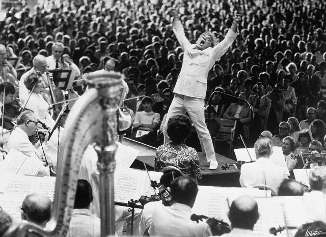 Leonard Bernstein and orchestra on a stage before thousands of people - he is wearing a white suit, arms outstretched and howling like a rock star