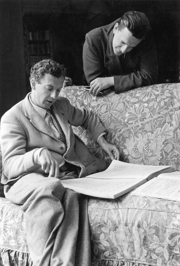 Britten studying music on a couch, with Peter Pears studying over his shoulder