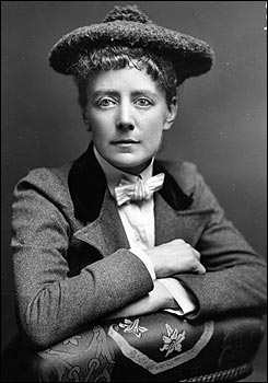 Ethel Smyth in a tweed coat and hat, arms folded over the back of a chair.
