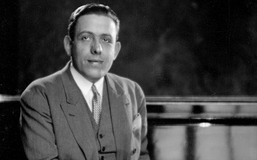 Poulenc in a suit under soft light with smoke rising from an unseen cigarette.