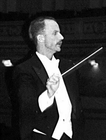 Tall, thin Dean Johnson in a tux conducting an orchestra.