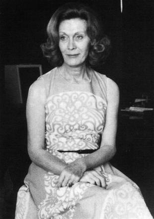 Angela Morley in a sleeveless Spring dress, arms folded on her lap.