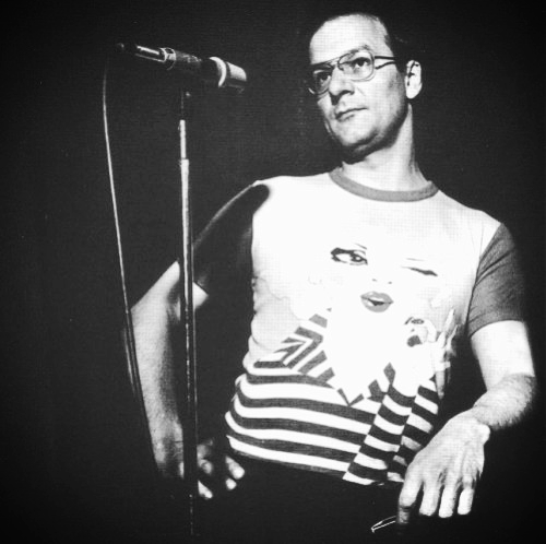 Vivier onstage behind a microphone looking sassy in a crazy printed t-shit.