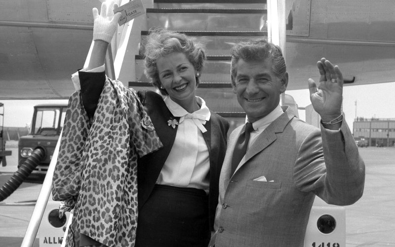 Bernstein and his wife having just disembarked from a plane, wave and smile for the camera
