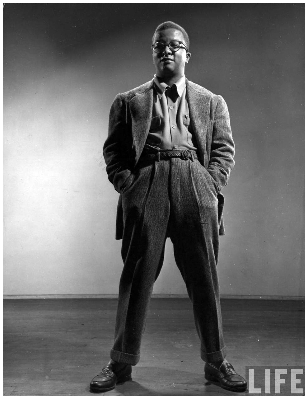 Billy Strayhorn standing tall in a wool suit with hands in his pockets. This photo was in Life Magazine sometime in the 40s.