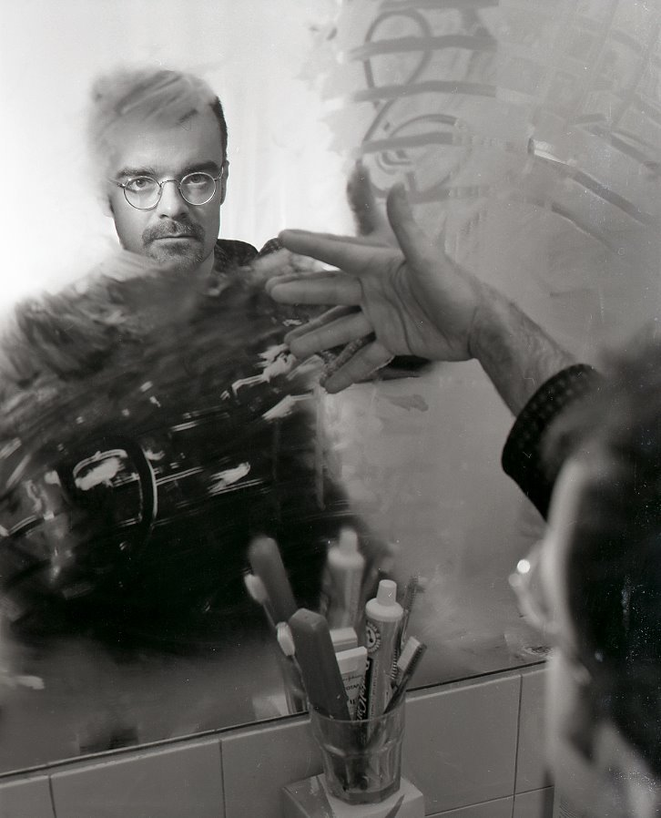 A yound Rodney Sharman looking at himself in a foggy bathroom mirror with a musical staff drawn in the condesation.