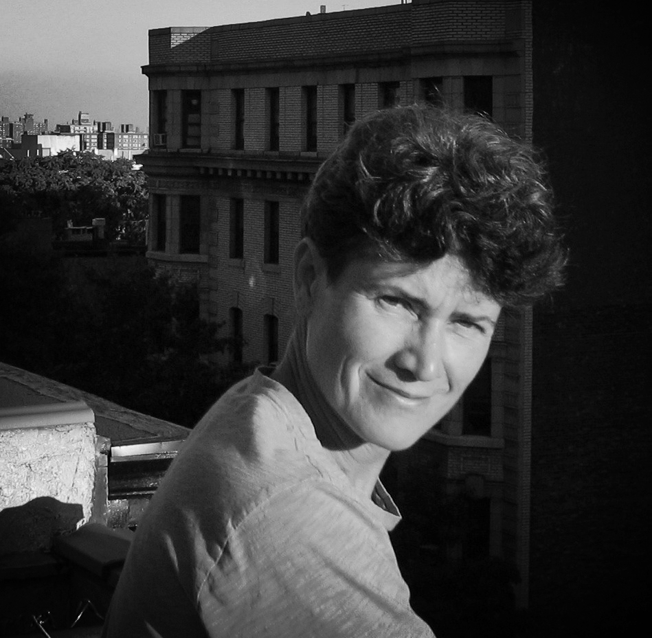 Paula Kimper squinting in a sunbeam on a rooftop.
